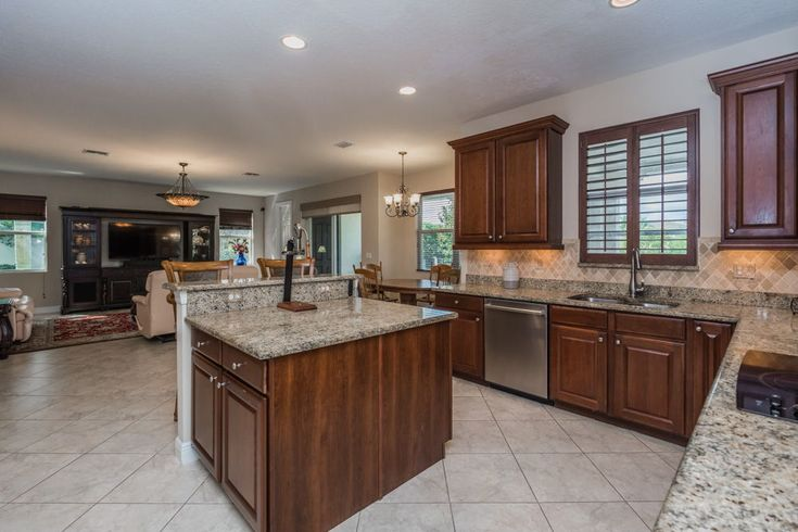 """The kitchen is open-concept and has spacious 42"""" cabinets with crown molding, granite countertops, stainless steel appliances, dual ovens, walk-in pantry, a breakfast area overlooking the pool, and a large center island with a snack bar."""