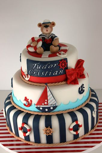 A children's birthday cake designed as a boating theme, sailboats, anchors, red and blue topped with a sailing teddy bear.