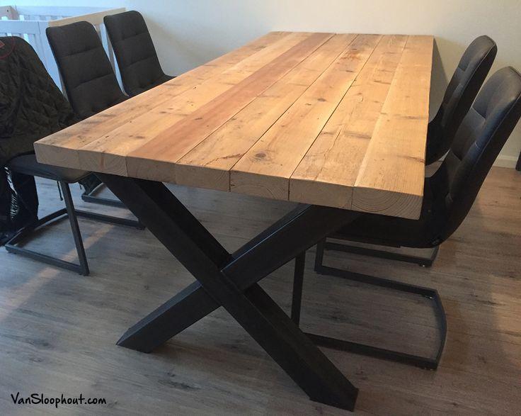 Oude grove houten balken die het blad vormen voor een tafel met stalen kruis…