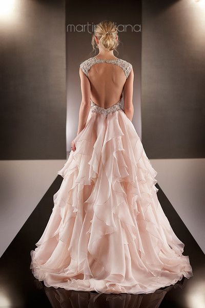 Blush pink organza A-Line wedding dress with figure-flattering asymmetrical ruched bodice, Diamante-encrusted cap illusion sleeves, an embellished keyhole back, and a decadent waist sash. Airy, cascading ruffles adorn the skirt and chapel train - also available in ivory {Dress by Martina Liana by @essensedesigns}