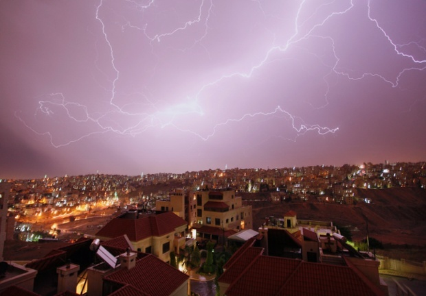 A spectacular thunderstorm lights the skyline in Amman, Jordan, as temperatures dropped to 20 degrees Celsius. Photograph: Mohammad Hannon/AP