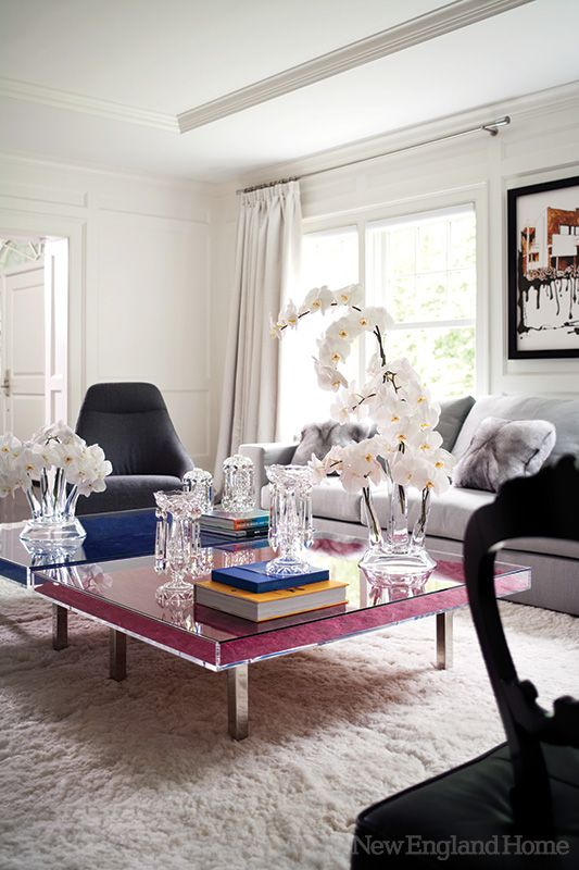 In the living room, colorful twin cocktail tables by French artist Yves Klein are set against a lush white alpaca rug from Peru.