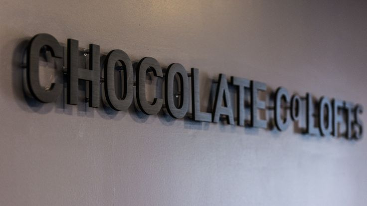 Black anodized cut aluminum pinned letters, displayed at The Chocolate Co. Lofts, Toronto, ON.