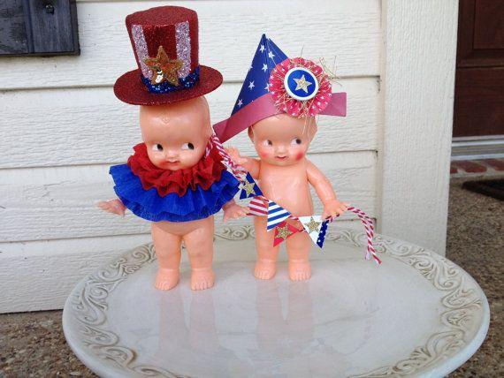 Décoration de la quatrième de juillet. Jour de l'indépendance ornement patriotique  Une poupée vintage est tout habillée pour le jour de l'indépendance. Il est coiffé d'un chapeau de papier et tenant une bannière décorative. La chaîne sur la bannière peut varier.  environ 7 pouces de haut  Vintage en plastique dur Irwin Kewpie doll 1950  s  poupée patriotique