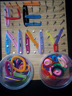 its a board with nails nailed into it in a grid, and with a container of hair bands with which you can create pictures, make letters, write words or numbers, etc... on the nails.