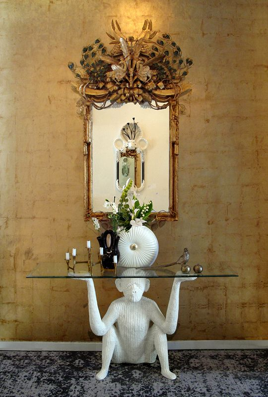 The monkey table, the gilded wallpaper, the table vignette, and, most of all, the objet trouve mirror by Codor Design.