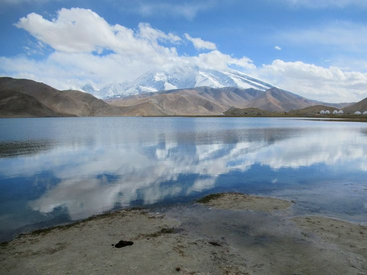 Muztagh-Ata, second highest mountain (7,509 meters) in the Pamir Range. is reflected in the waters of Lake Karakol, the highest lake (3,600 meters) on the Pamir Plateau.
