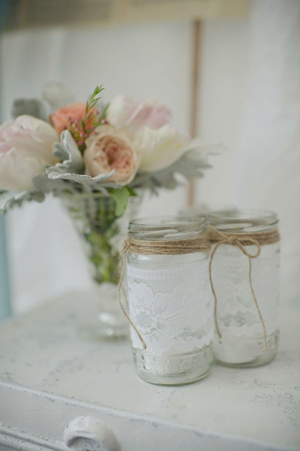 Pastel flowers in a vase and mason jars with twine tied in a bow and lace.