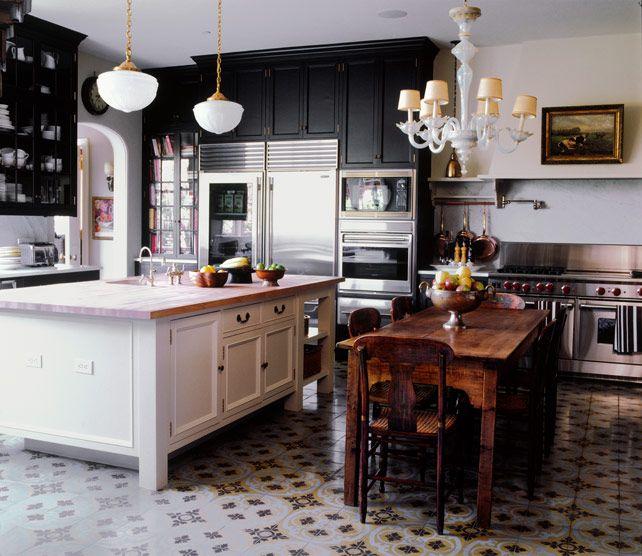 Dark cabinets on the perimeter with white butcher block island. Cement tile floors. Kristen Buckingham