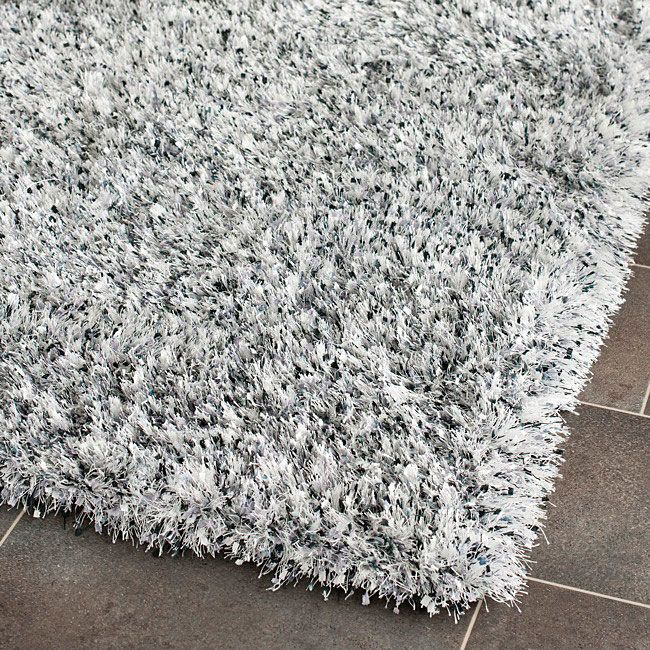 Fia's room? Overstock This hand-tufted polyester shag rug offers luxurious comfort and modern style. High-density polyester pile with boxed-strands peppered across features a silver with charcoal grey and metallic blue accents background.