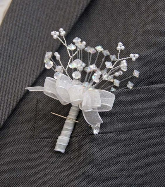 A modern style Groom's wedding buttonhole with light catching crystals and small bead branches on a silver wire, with a narrow 9mm white organza ribbon bow and with a matching ribboned stem to finish this buttonhole. http://www.sarahsflowers.co.uk/buttonholes/groom-39-s-party/white-ribbon-grooms-crystal-bead-buttonhole-with-diamantie-pin/prod_7153.html