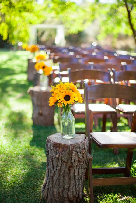 Tree stumps and flower arrangements down the aisle (No sunflowers for you off course!!)