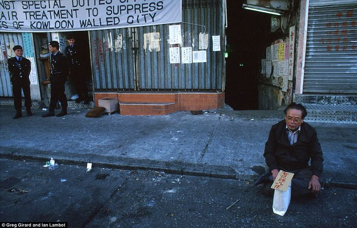 A Kowloon Walled City resident who is dissatisfied with compensation payouts from the government sits on a pavement in protest as police sta...