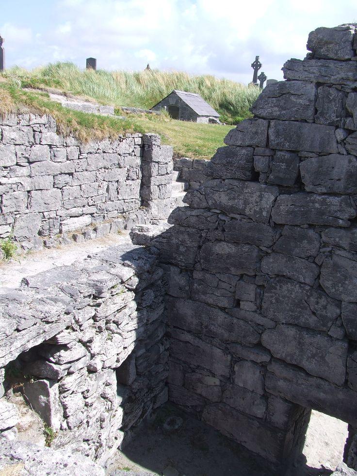 """A igreja de São Caomhán de Inisheer, o santo padroeiro da ilha, com o túmulo de Caomhán (Leaba Caomhán) ao fundo. Em Inisheer, nas ilhas Adan, baía de Galway, Irlanda. São Caomhán tem um alto respeito pelos insulares que usam o termo """"Ara Chaomhain"""" que significa """"Nosso querido amigo Caomhan"""" ao se referir a ele.   Fotografia: Laurel Lodged."""