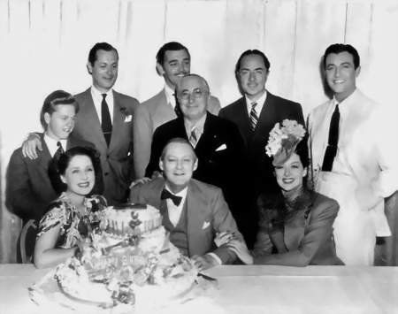 Mogul Louis B. Mayer (1884-1957) surrounded by MGM stars : Seated - Norma Shearer (1902-1983), Lionel Barrymore (1878-1954) and Rosalind Russell (1907-1976).  Standing : Mickey Rooney  (1920-2014), Robert Montgomery (1904-1981), Clark Gable (1901-1960), Mayer, William Powell (1892-1984) and Robert Taylor (1911-1969)