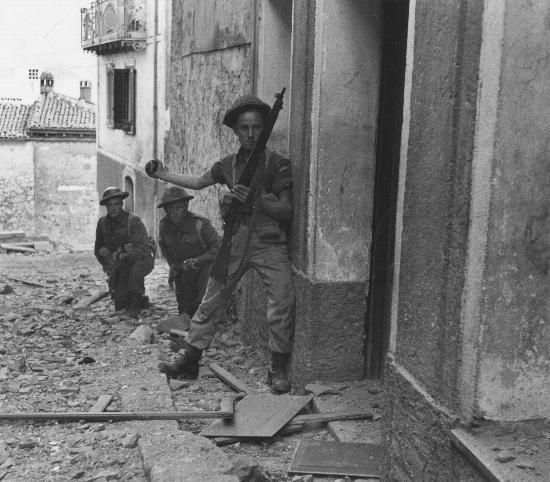 Three men of the Carleton and York Regiment, Canadian Infantry Brigade, preparing to send a hand grenade into a sniper's hideout in the Matese Mountains. Campochiaro, Italy. October 23, 1943.