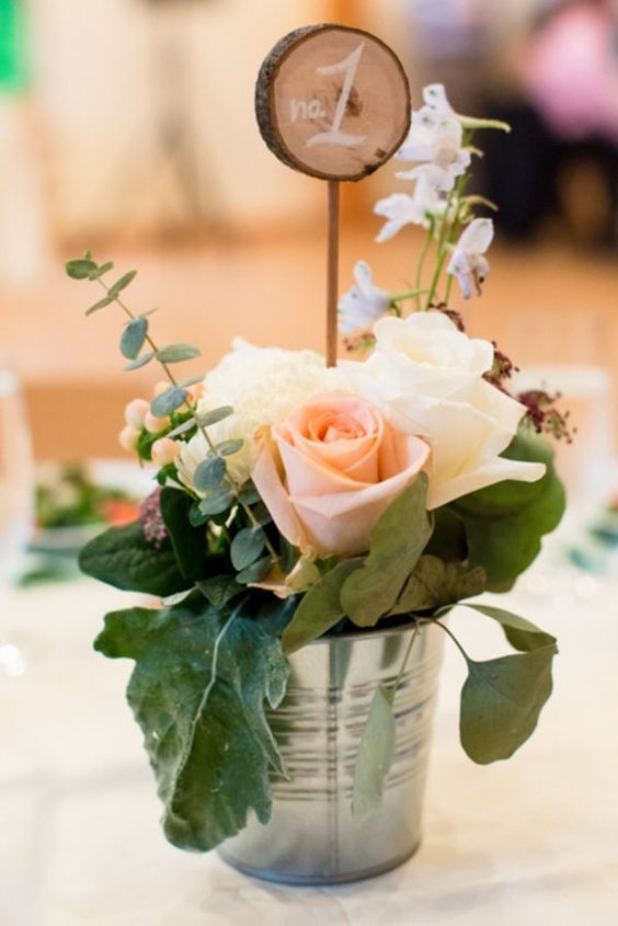 galvanized bucket with blush roses and leaves and a wood slice table number