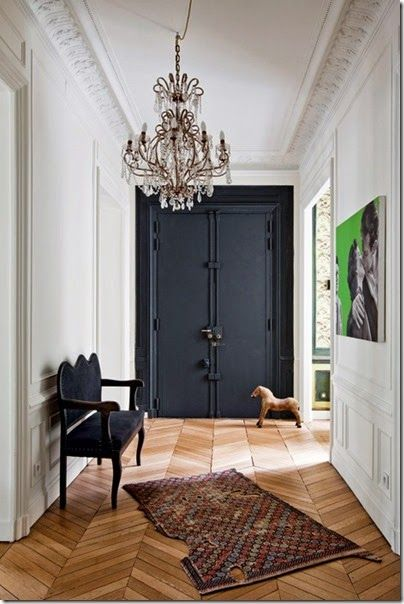 Chevron patterned wood flooring, crystal chandelier, accompanied with black double vault doors bring this hallway to life.
