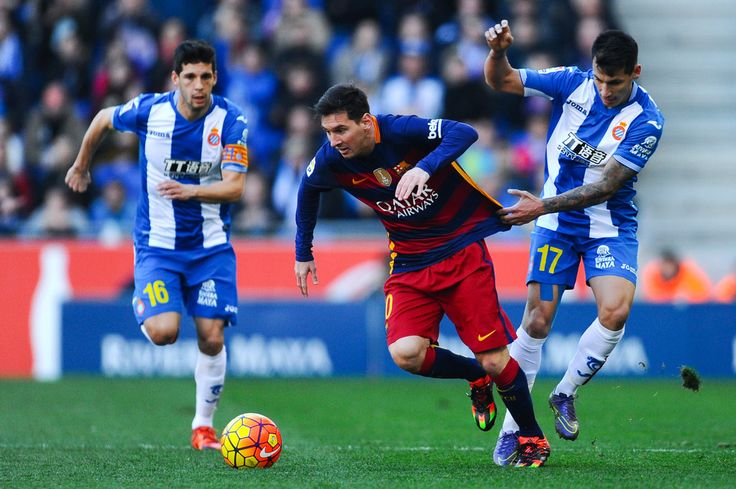 Lionel Messi of FC Barcelona competes for the ball with Hernan Perez (R) and Javi Lopez of RCD Espanyol during the La Liga match between RCD Espanyol and FC Barcelona at Cornella-El Prat Stadium on January 2, 2016 in Barcelona, Catalonia.