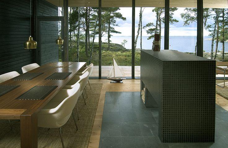 Полностью остекленная стена стирает барьер между внутренним и внешним пространством дома впуская окружающую природу в дом и открывая вид на залив. .