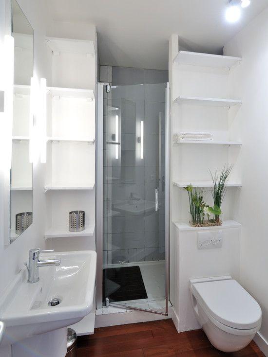 Banheiro branco com prateleiras em cima do vaso sanitário