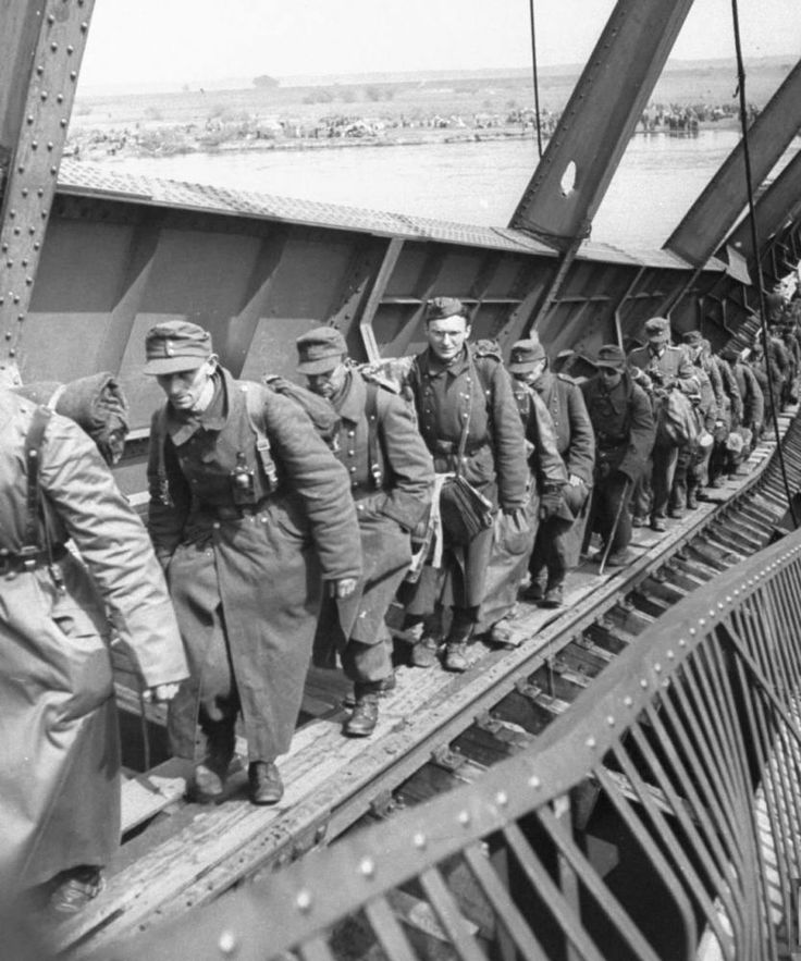 German soldiers walk along a precarious platform spanning a ruined bridge over the Elbe River to surrender to US forces instead of Russian troops in the waning days of WWII. May 1945 Tangermunde, Germany. In the closing days of the war, the Germans resorted to a veritable Marathon to reach Allied lines as the Russians bulldozed their way toward Berlin.