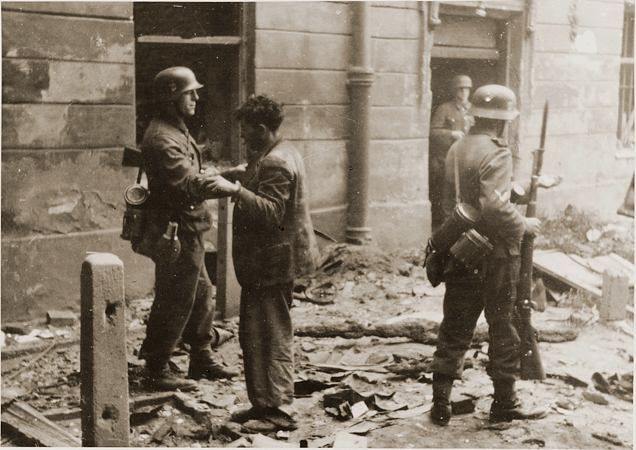 """An SS soldier searches a captured Jewish resistance fighter during the suppression of the Warsaw ghetto uprising. The original German caption reads: """"Pulled from a bunker."""""""