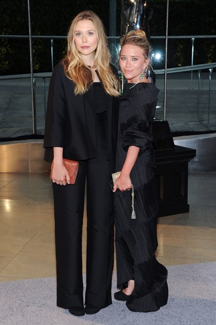 Elizabeth Olsen wore a dress and carried a clutch from her sisters' label, The Row, while Mary-Kate Olsen wore a vintage Issey Miyake dress.