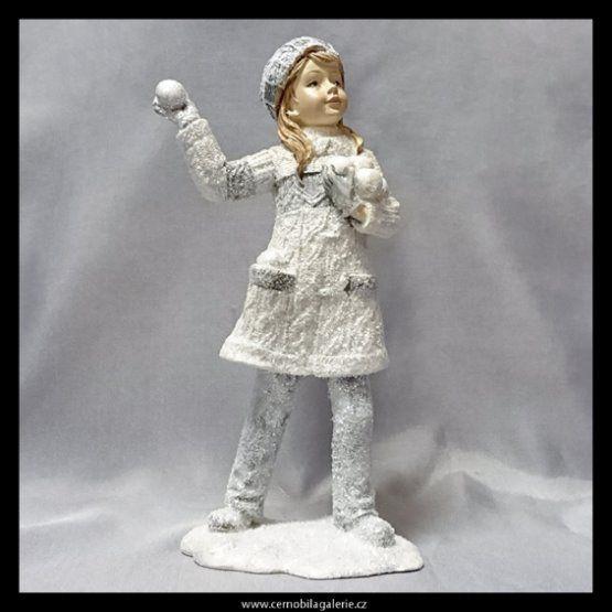 Dekorační figurka koulující se dívky ve svetru.