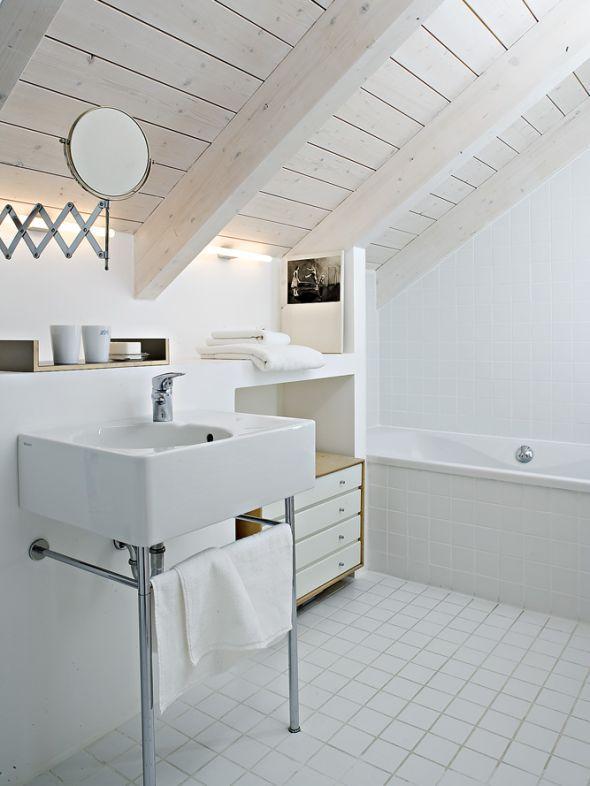 Eine Vorwandinstallation für die Waschbecken schafft zwei Nischen: für die Wanne auf der einen und das WC auf der anderen Seite.