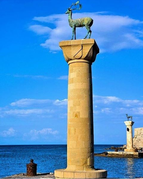 """A pair of bronze deer statues flank the inlet to Mandraki Harbor in Rhodes where, according to tradition, the Colossus of Rhodes stood.  Colossus of Rhodes was one of the seven wonders of the ancient world. It was a lighthouse in the form of a giant human figure that straddled the entrance to Mandraki Harbor. Ships entering Rhodes sailed between the legs of the giant. In 226 BC a strong earthquake toppled the Colossus. In its place today are a pair of statues of the symbol of Rhodes - a…"