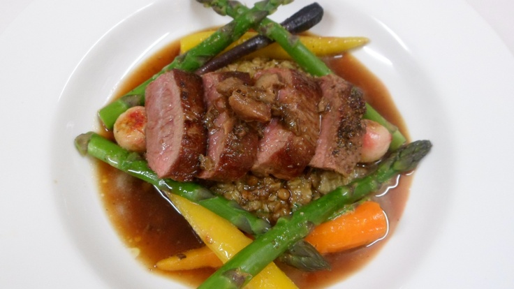 Seared lamb loin with creamy brown lentils, spring vegetables with lemon dressing and a lamb shoulder jus.