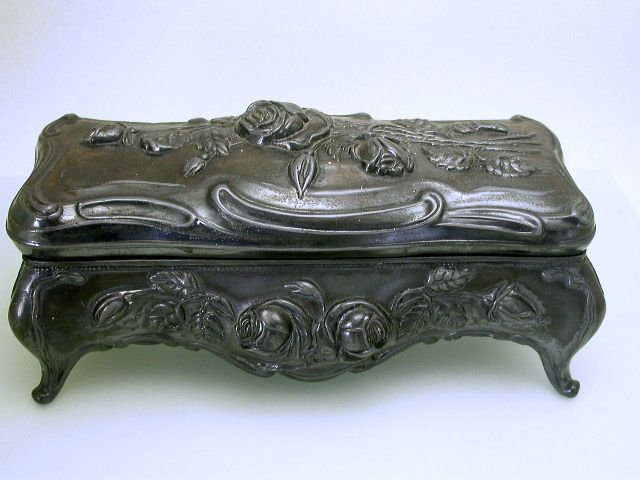 Beautiful & bold, large size footed jewelry casket or glove box with Repousse roses on lid and all 4 sides. Signed on bottom,but only a portion of the mark can be seen, it is probably N.B. Rogers of Danbury, Ct. circa 1905, Art Nouveau Period.  This gorgeous jewelry box measures 9 3/8″ wide at the feet, 4″ deep at the thickest point and 3 3/4″ tall | JV