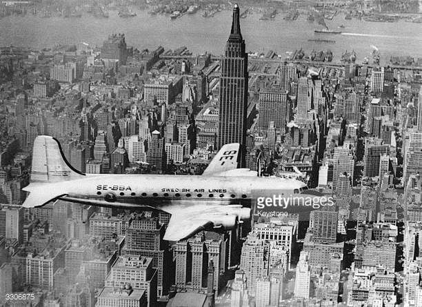 The first Swedish airline passenger plane a DC4 flies up the East River New York en route to la Guardia Airport The Empire State Building can be seen...
