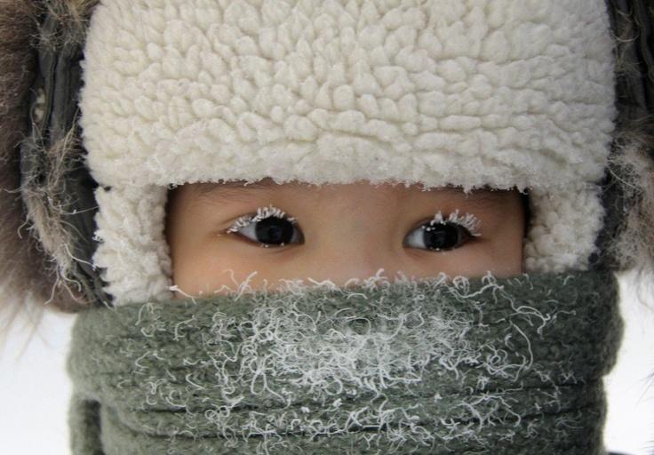 Dziecko z pokrytymi szronem rzęsami na ulicy wschodniosyberyjskiego miasta Jakuck, 10.02.2012 r. Temperatura w Jakucku wynosiła ok. - 35 stopni Celsjusza.