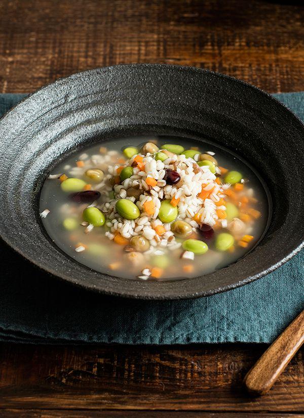 もち麦とお豆のスープリゾット    もち麦が「腸活」に役立ち、たんぱく質も豊富に摂れ、ごま油の風味とスパイスが食欲をそそります。 (0.3Lサイズ使用) 材料  もち麦 大さじ2 ミックスビーンズ 30g 枝豆(冷凍) 正味30g にんじん 20g しいたけ 1枚 しょうがのみじん切り(チューブでも可) 3g 鶏がらスープの素 小さじ1弱 黒こしょう 少々 ごま油 少々 沸とうしたお湯 適量  作り方  1.にんじんは皮をむいて5㎜角に切り、もち麦と共にスープジャーに入れて沸とうしたお湯を注ぎ入れ、フタを閉めずに3分ほど置く。 2.枝豆は解凍して中身を取り出し、しいたけは石づきを取って5㎜角に切り、軸は5㎜幅に切る。 3.(1)のお湯を切り、材料をすべていれて沸とうしたお湯を注ぎ入れ、1時間30分以上保温する。