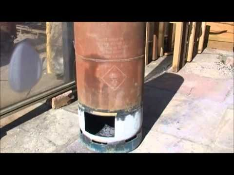 Rocket stove heater built in firebox. - YouTube | I like this one. No thermal mass, but compact enough for a small room. Would look great with off-white enamel.