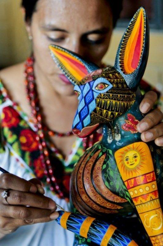 """Alucinacion de Copal: Reyna nos dice: """"Un alebrije es un ser con vida, porque viene de la naturaleza, por eso no hay que lastimar la pieza, hay que pasarle buena vibra"""" mientras decora serenamente la pieza, ella vive junto a su esposo Zeny, en San Martin Ticajete en Oaxaca, ocupando la corteza del árbol de copal dan vida a lo que Zeny llama sus """"alucinaciones"""" el nos dice: """"las mismas ramas te dicen la forma que van a tomar, es cuestión de contemplarlas bien""""."""