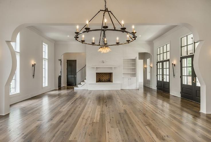 Mediterranean home features an arched doorway leading to the living room filled with a white brick fireplace next to a built-ins flanked by windows to the left and a row of black double doors to the right.