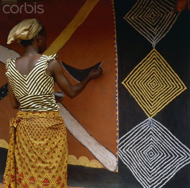 Africa | 'Woman Painting a Mural' Nwunnan uses natural pigments to decorate the wall of a village dwelling. Her pattern on her blouse echoes that of the traditional, diamond-shaped, motif, known as ogalu, which is incorporated into the mural. Nri, Nigeria. | © Margret Courtney - Clark