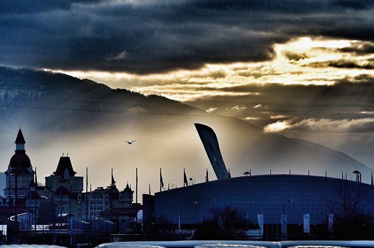 Early morning sunlight breaks through the clouds behind the Olympic cauldron