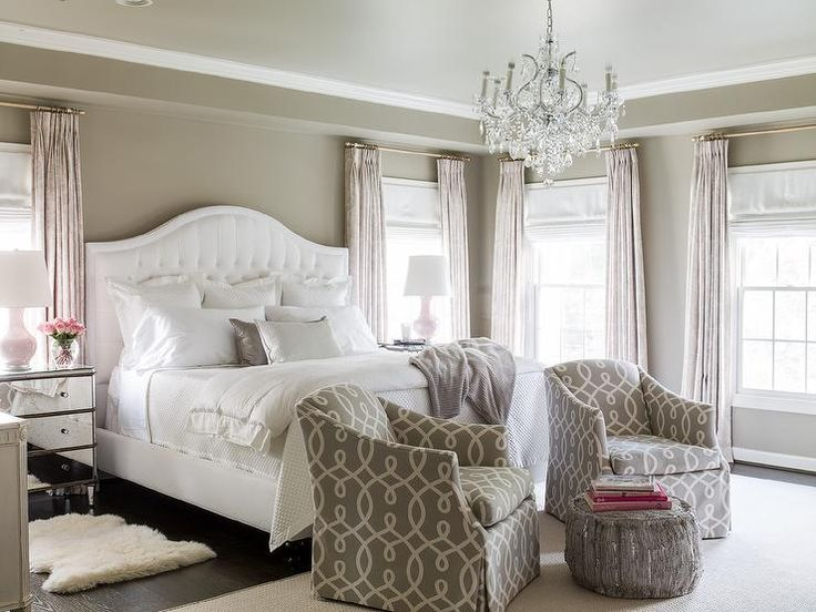 Pink and gray bedroom features gray walls lined with a white tufted camelback bed dressed in white ...