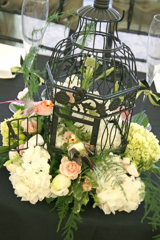 """Create a stunning centerpiece in a black bird cage with hydrangea, roses, and greenery.  Take it one step further for a pop of color and """"put a bird on it."""" Flowers by A Floral Affair - www.afloralaffair.com #wedding #event #flowers"""