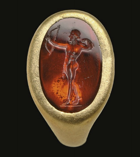 A ROMAN GOLD AND GARNET FINGER RING   CIRCA 1ST CENTURY A.D.   The plain hollow hoop flat on the interior, rounded on the exterior, with an oval bezel set with a flat garnet, engraved with Apollo, depicted nude, his right arm raised holding a bow, reaching for an arrow from his quiver with his left, raised up on his toes, his right leg behind and slightly bent, a wreath in his hair, on a short groundline