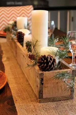 centrotavola natale con scatola di legno, pigne, candele, rametti verdi