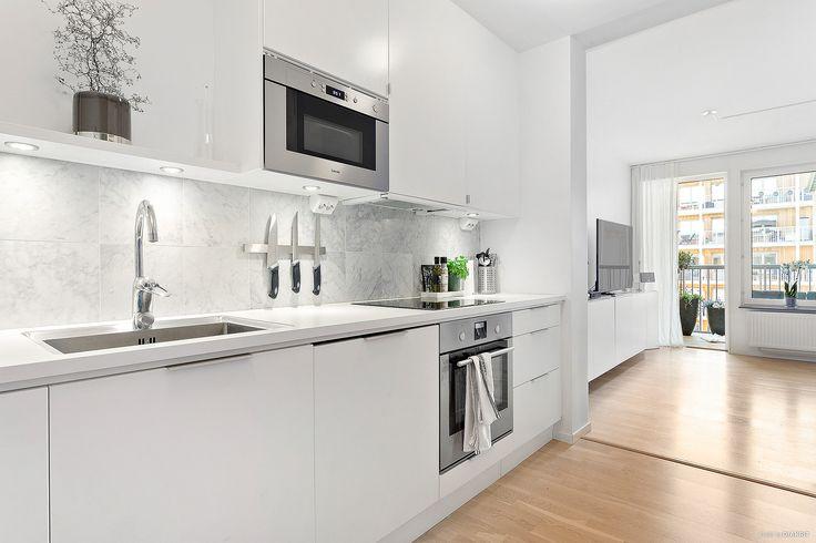Köket har vita luckor och stilrena handtag. Stänkskyddet ovanför den ljusa bänkskivan med underlimmad diskho är i ljus carraramarmor. Arbetsytorna är rejält tilltagna med gott om förvaring | Ballingslöv