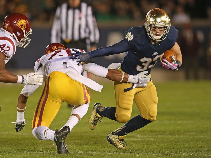 Cam McDaniel #33 of the Notre Dame Fighting Irish breaks a tackle by Su'a Cravens #21 of the University of Southern California Trojans at Notre Dame Stadium on October 19, 2013 in South Bend, Indiana.