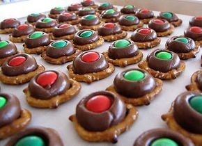 Pretzel buttons Small pretzels Hershey Kisses M&Ms Top each pretzel with a Hershey kiss and placed in a preheated 200-degree oven for 10 minutes. Remove and immediately press an M&M on top of each.