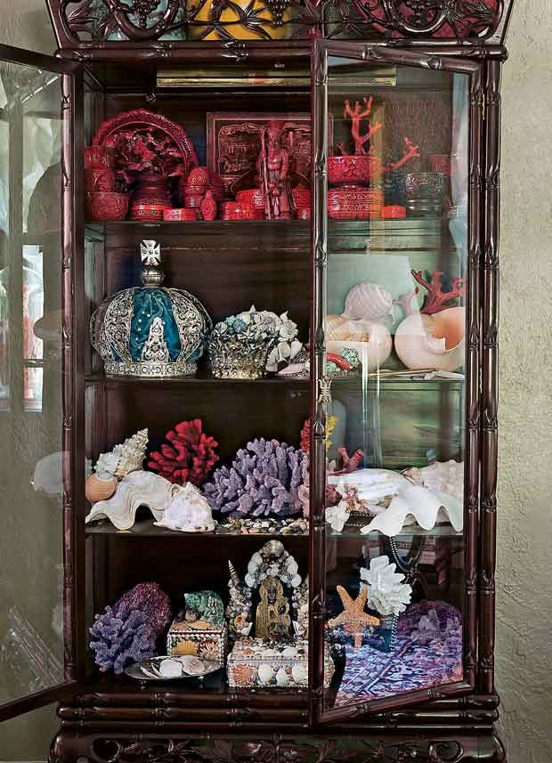 Faux bamboo cabinet of curiosities is an Asian piece dating to the 1920s that displays everything from Mardi Gras crowns to cinnabar, shells & coral.