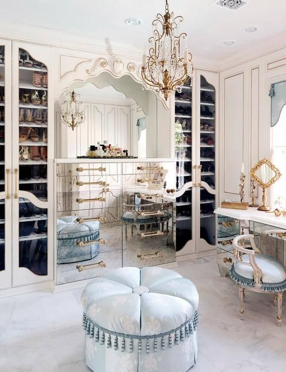 French walk in closet features an alcove filled with an antiqued mirrored dresser adorned with gold pulls flanked by glass front shoe cabinets.